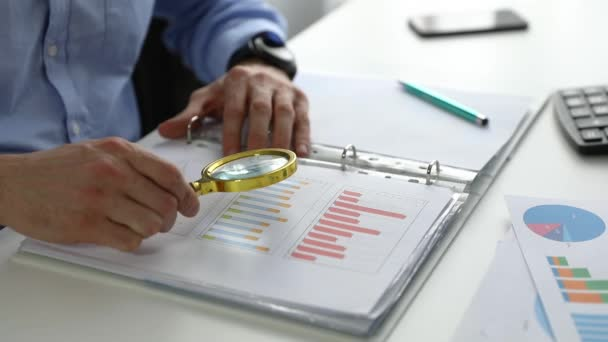 internal audit concept - auditor with magnifying glass inspecting business finance documents