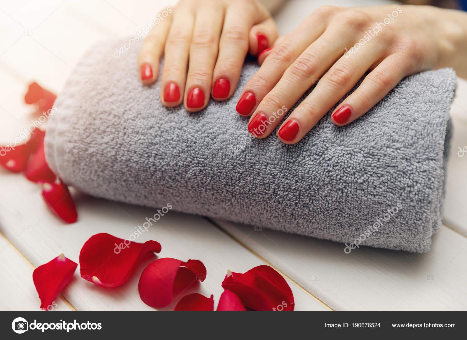 las uñas de mujer con esmalte de uñas rojo en toalla rollo a hombre ...
