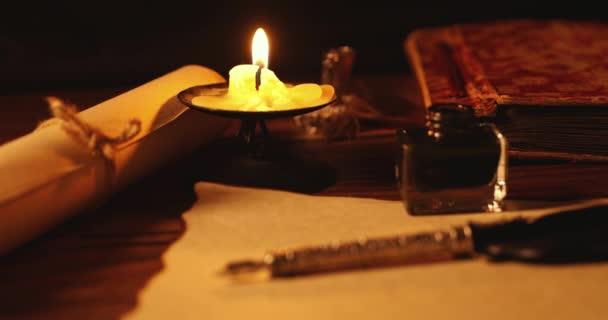 Federkiel und Tintenfass auf altem Pergamentpapier im Kerzenschein