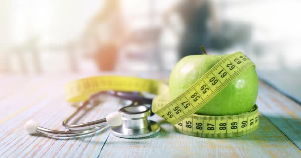 healthy lifestyle and nutrition - apple with measurement tape and stethoscope on the table in gym with running people in background