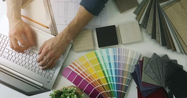 návrhář pracující na notebooku v kanceláři pro nový design interiéru. pohled shora