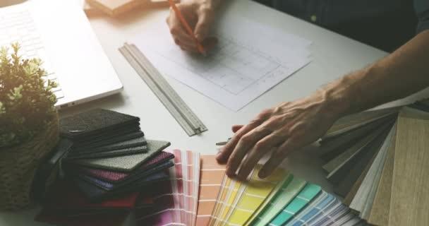 návrhář, který provádí výběr barvy ze vzorníku pro domácí design interiéru