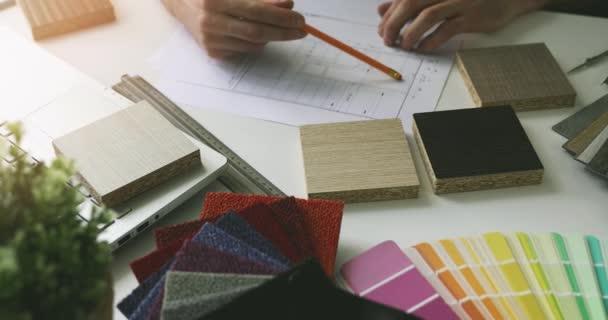 návrhář pracující v kanceláři, který provádí výběr nábytku ze vzorků pro projekt bytového interiéru