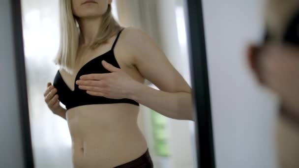 young woman in black bra checking her breasts in front of the mirror