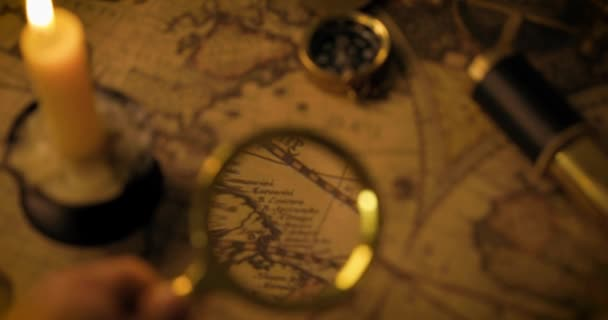 exploration and adventure concept - hand with magnifying glass searching on vintage world map