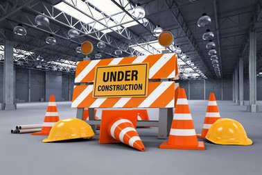under construction sign with barrier and cones