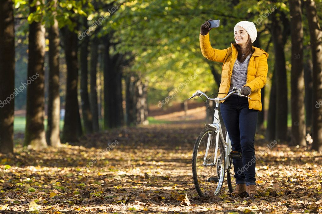 girl on bike taking photos with cell phone outdoors