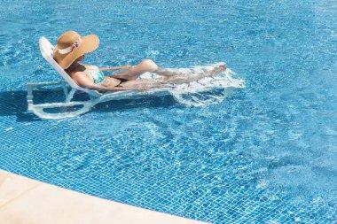 Beautiful woman on sun lounger and taking sunbathe
