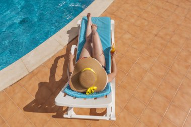 woman in hat resting in the edge of a swimming pool