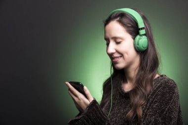 Young girl choosing a music on her smartphone to listen