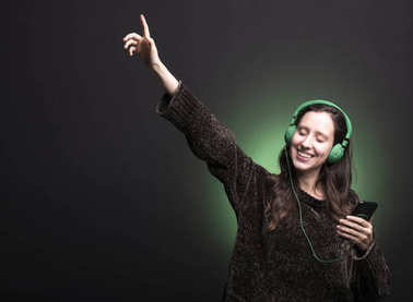 Young girl listening music with headphones and dancing on green background
