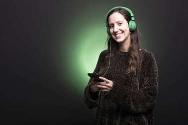 Cute young girl listening music with green headphones