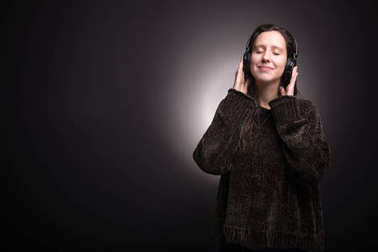 Cute girl listening to music with headphones with eyes closed
