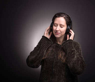Beautiful girl listening to music with headphones with eyes closed