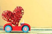 Fotografie hračka auto přináší srdce na Valentýna na pozadí