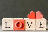 Fotografia cuori rossi in legno decorativi con i cubi di amore, San Valentino di ortografia concetto di giorno
