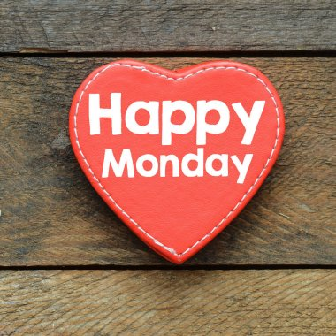 Closeup of red heart with text Happy Monday over wooden surface