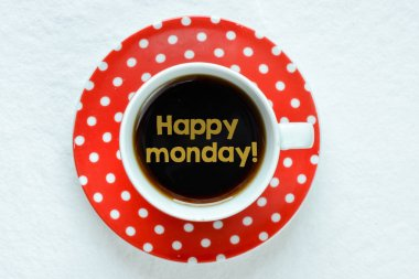 Closeup of  cup of coffee with text Happy Monday inside
