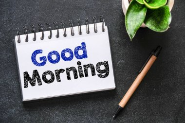 Good morning note in notepad on table