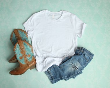 White T Shirt Flat Lay Mockup on aqua background with cowboy boots and ripped jeans