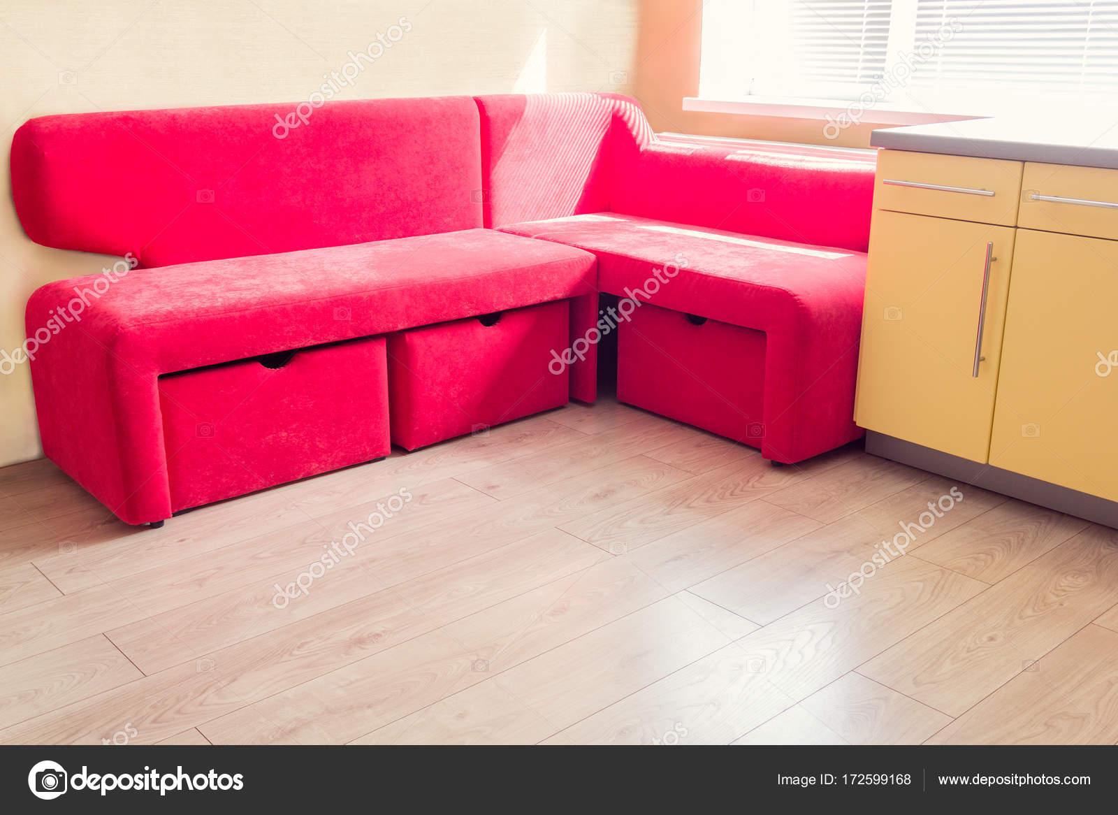 Gelbe Küche mit Schränke, Fenster, Laminat und roten weichen cou ...