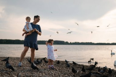 Young mother with her baby girl daughters feeding swan and little ducklings birds bread at a river wearing dotted dress - Family values warm color summer scene