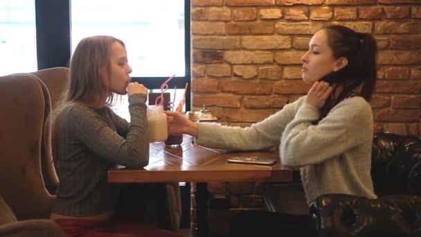 Két lány turmixot iszik egy kávézóban. Városi életmód