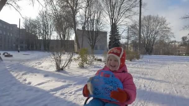 Mädchen fährt Schlitten durch den Schnee