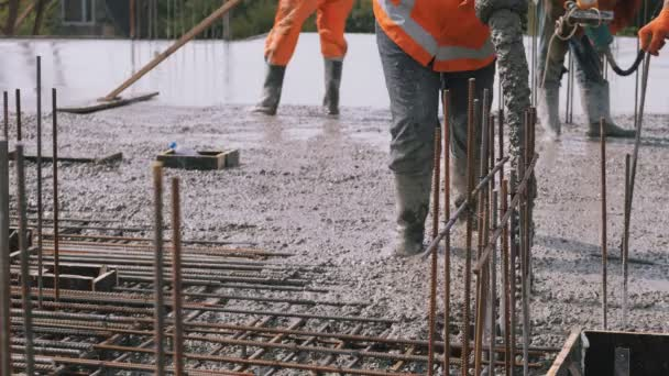 Železobetonové bednění, pracovnice nalévající na staveniště.
