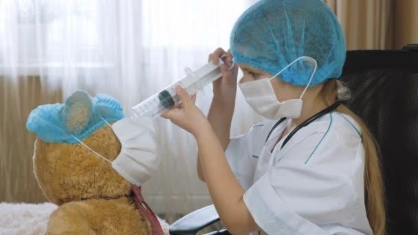 Kleines Mädchen mit Thermometer und Spritze spielt im Krankenhaus Arzt, Krankenschwester.