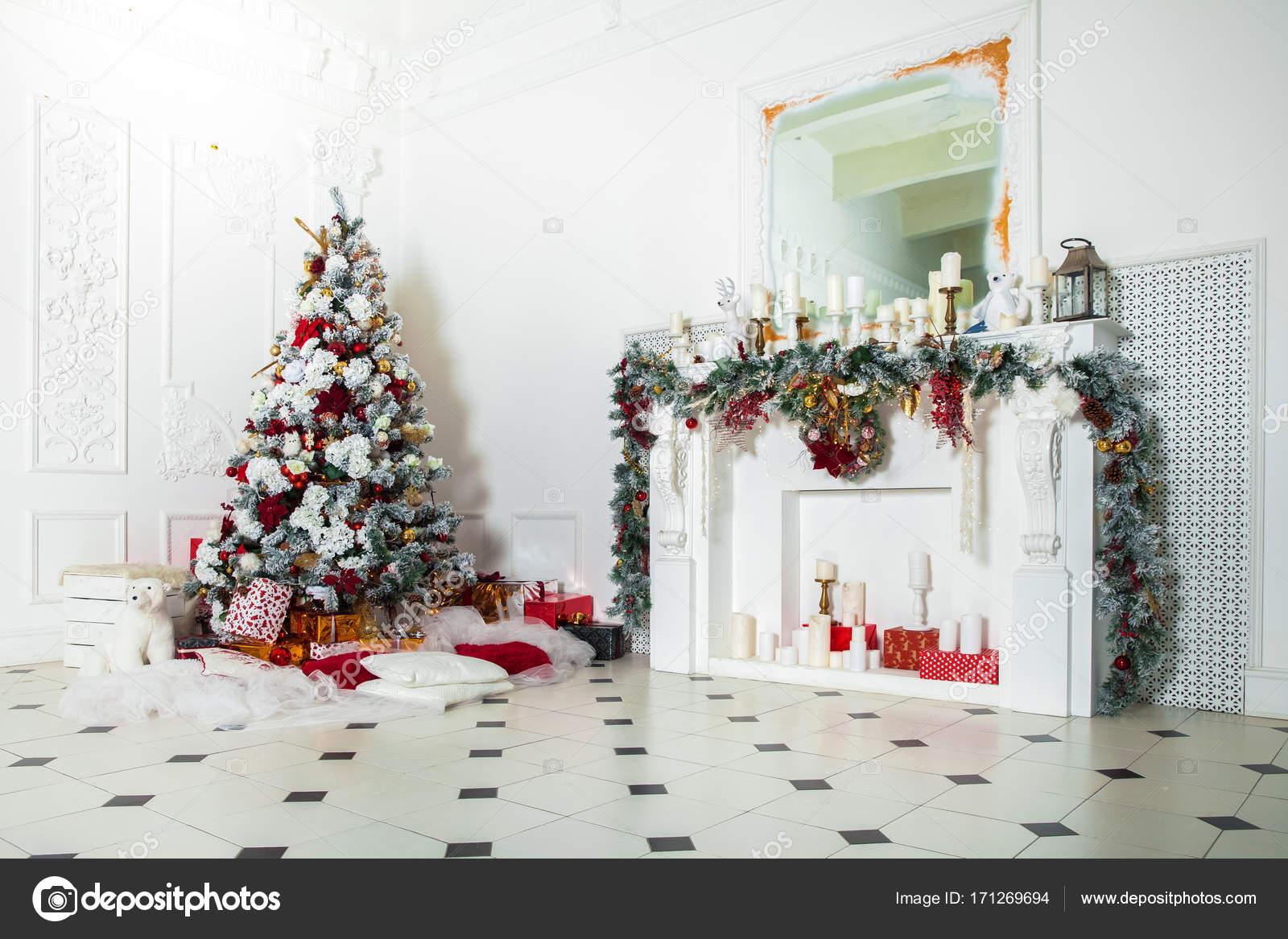 klassieke witte kerst interieur met nieuwe jaar boom versierd open haard met grijze stoel klokken aan de muur en presenteert onder de boom foto van