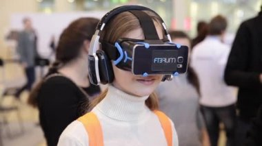 Girl uses virtual reality game development kit, virtual reality glasses