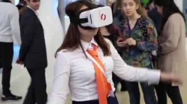 Young girl playing with virtual reality glasses in game center