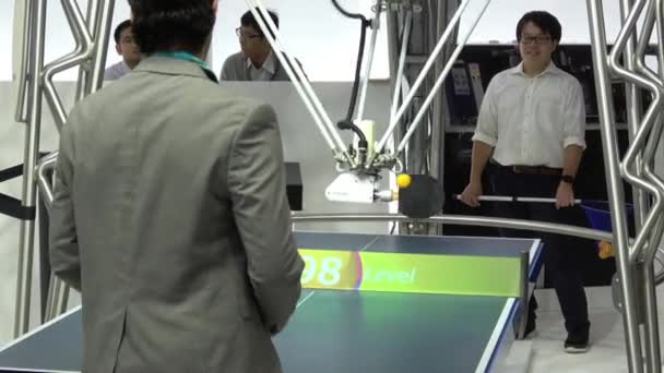 Robot playing ping-pong table tennis on Omron stand on Messe fair in Hannover, Germany