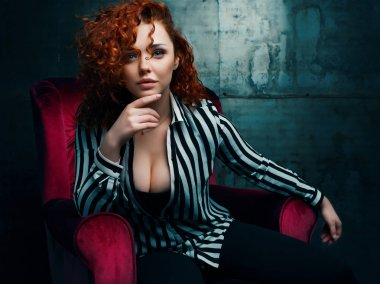 Curly woman siting on red chair