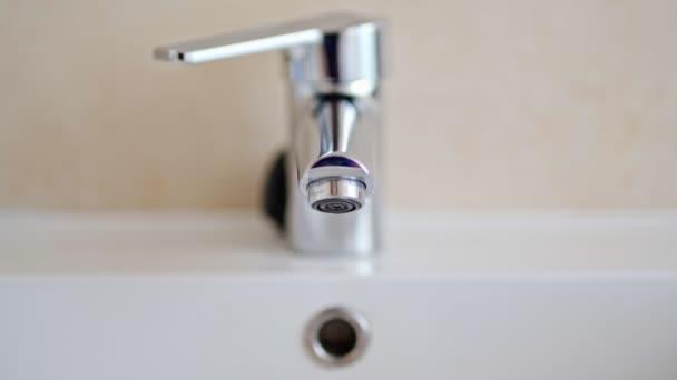 Muž otvírá kohoutek a plní dřez vodou. Voda tekoucí z chromového kohoutku. Instalatérství koupelen.