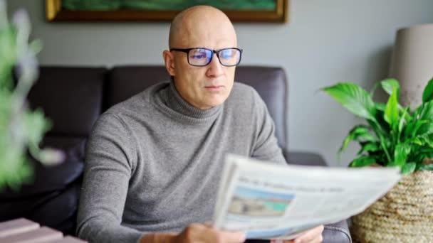 novinky, tisk, média, svátky a lidé koncept - muž čtení novin doma.