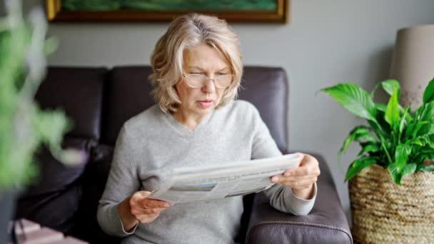 novinky, tisk, média, svátky a lidé koncept - žena čte noviny doma.