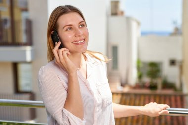 Portrait of a smiling casual woman holding smartphone on the balcony.