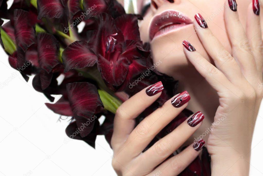 Burgundy manicure with gladiolus. — Stock Photo © marigo #129846290