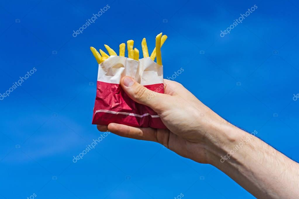 Crispy french fries in a paper bag in a male hand on a blue sky background.