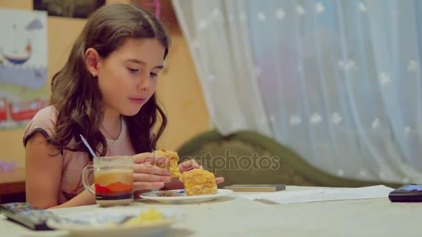 dospívající dívka, pít čaj a jíst dort, vnitřní životní styl sledování televize tv u snídaně večeře