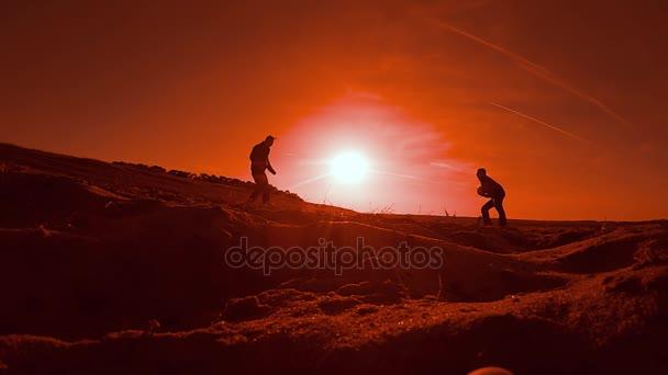 dva muži fotbal fotbalový hráč hraje s míčem při západu slunce na siluetu