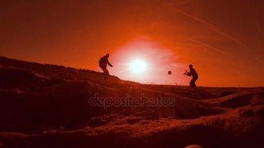 fotbal. dva muži fotbal fotbalový hráč hraje s míčem při západu slunce na siluetu