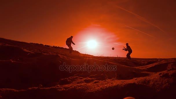 foci. két ember soccer labdarúgó labdát naplemente alatt a sziluett
