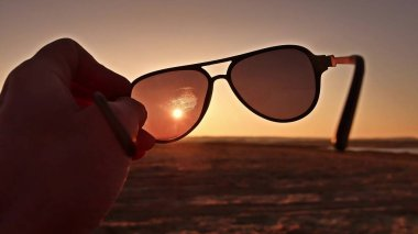 travel. Hand holds sunglasses at sunset lifestyle nature
