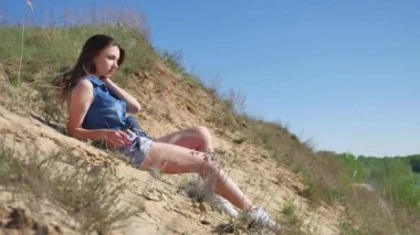 Girl is lying on the sand. Beautiful girl on nature lifestyle hill