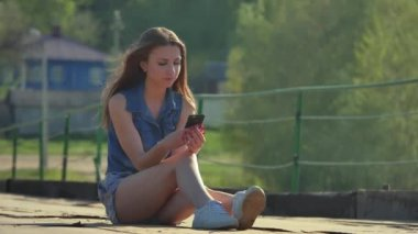 The girl is holding a smartphone. Internet girl in smartphone social media sits on iron bridge outdoor