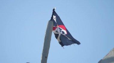 Jolly Roger Pirate flag develops against the blue sky