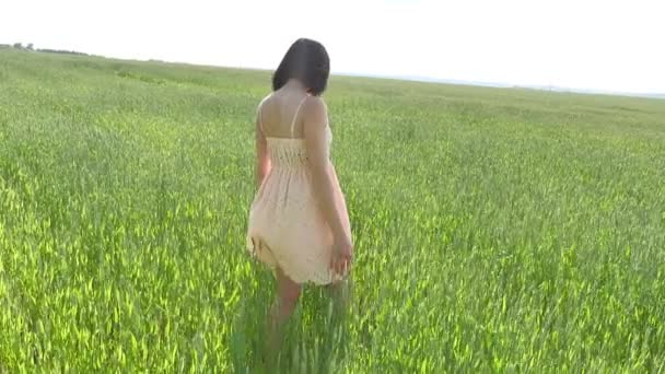 Girl field wheat. Beautiful girl walking on a green field with wheat, grass nature lifestyle